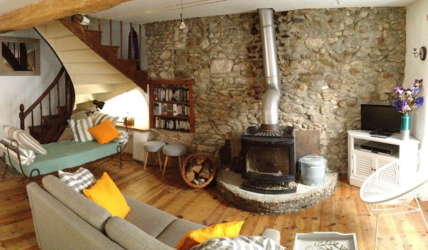 French house southern France rental Exposed stone wall log burner living room